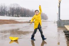 Um menino em uma capa de chuva do amarelo joga um barco do grande papel em uma poça Foto de Stock