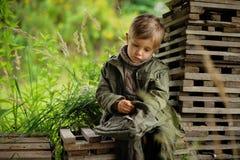 Um menino em um vestido militar imagens de stock royalty free