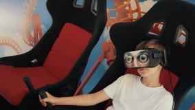 Um menino em vidros da realidade virtual senta-se em uma poltrona em uma atração O conceito das tecnologias as mais novas vídeos de arquivo