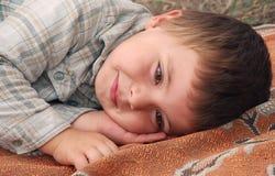 Um menino encontra-se e sorri-se imagens de stock