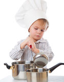 Um menino engraçado está retratando um cozinheiro fotografia de stock