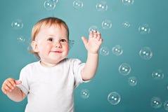 Um menino engraçado pequeno está jogando com bolhas Imagem de Stock Royalty Free
