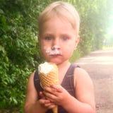 Um menino está comendo um gelado imagens de stock