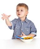Um menino está comendo o cereal de uma bacia Foto de Stock Royalty Free