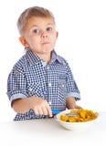 Um menino está comendo o cereal de uma bacia Imagem de Stock