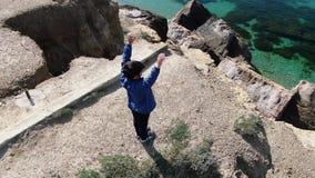 Um menino está de espalhamento seus braços no litoral que o sol brilha em sua cara o vento filme