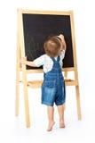 Um menino está desenhando em um quadro-negro foto de stock royalty free