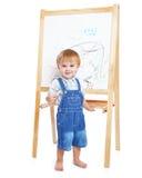 Um menino está desenhando em um quadro-negro Imagem de Stock Royalty Free