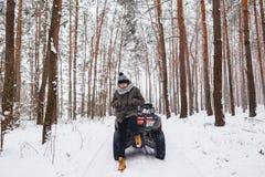 Um menino está estando perto de uma bicicleta do quadrilátero no meio da floresta fotografia de stock