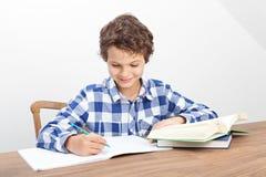 Um menino está fazendo seus trabalhos de casa Fotografia de Stock Royalty Free
