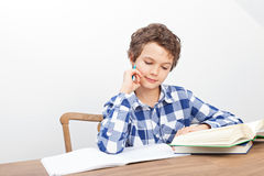 Um menino está fazendo seus trabalhos de casa Imagem de Stock Royalty Free