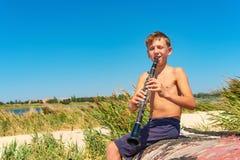 Um menino está jogando em um clarinete preto que senta-se em um barco de madeira velho na praia foto de stock