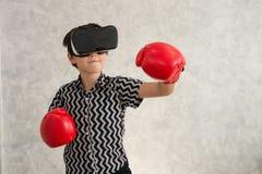 Um menino está jogando o jogo do encaixotamento com os auriculares da realidade 3D virtual Foto de Stock