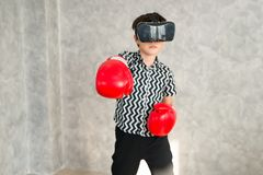 Um menino está jogando o jogo do encaixotamento com os auriculares da realidade 3D virtual Imagem de Stock
