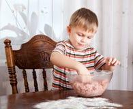 Um menino está misturando o mincemeat em uma bacia foto de stock