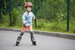 Um menino está montando em rolos Imagens de Stock