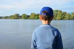 Um menino est? pelo lago e pelos olhares da floresta na ?gua calma Natureza, projeto, inspira??o, exterior Caminhada fora imagens de stock