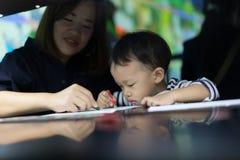 Um menino está pintando com sua mamã Foto de Stock