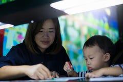 Um menino está pintando com sua mamã Fotografia de Stock