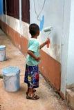 Um menino está pintando na parede imagem de stock
