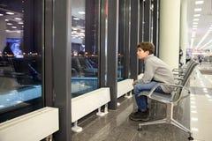 Um menino está situando no salão do aeroporto fotos de stock