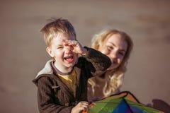Um menino está sorrindo fechando seu olho com a mão Fotografia de Stock Royalty Free