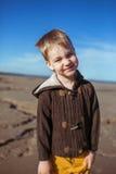 Um menino está sorrindo para a câmera na praia Imagens de Stock