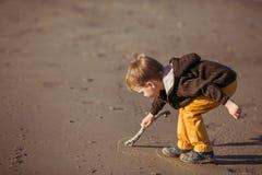 Um menino está tirando na areia com uma vara Foto de Stock Royalty Free