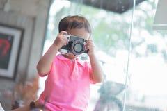 Um menino está tomando uma câmera do filme da foto fotos de stock