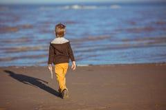 Um menino está vindo ao mar com uma vara em sua mão Imagem de Stock Royalty Free