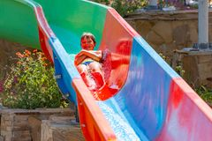 Um menino feliz na corrediça de água em uma piscina que tem o divertimento durante férias de verão em um parque bonito do aqua um fotografia de stock royalty free
