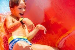 Um menino feliz na corrediça de água em uma piscina que tem o divertimento durante férias de verão em um parque bonito do aqua um fotografia de stock