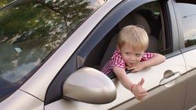 Um menino feliz pequeno está sentando-se atrás da roda de um carro e mostra seu polegar acima video estoque