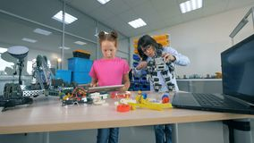 Um menino fixa um robô quando uma menina trabalhar com uma tabuleta em uma sala do laboratório Conceito moderno da educação vídeos de arquivo