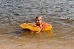 Um menino flutua em um círculo inflável Fotos de Stock