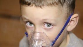 Um menino frio respira em um inalador