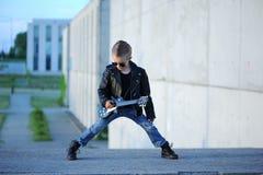 Um menino gosta de uma estrela do rock que joga a música na guitarra elétrica foto de stock