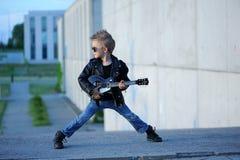 Um menino gosta de uma estrela do rock que joga a música na guitarra elétrica imagens de stock