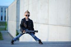 Um menino gosta de uma estrela do rock que joga a música na guitarra elétrica fotografia de stock