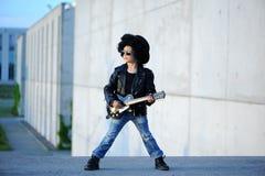 Um menino gosta de uma estrela do rock que joga a música na guitarra elétrica imagem de stock