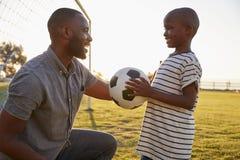Um menino guarda um futebol ao jogar com seu paizinho imagem de stock royalty free