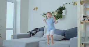 Um menino idoso de 4 anos com cabelo branco e saltos azuis e sorrisos de uma camisa no sofá Divertimento e bebê em casa Partida