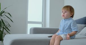 Um menino idoso de 2 anos senta-se em um sofá e olha-se a tevê ao sentar-se com o controlo a distância em suas mãos Desenhos anim