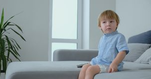 Um menino idoso de 2 anos senta-se em um sofá e olha-se a tevê sentar-se com um controlo a distância em suas mãos