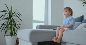 Um menino idoso de 2 anos senta-se em um sof? e olha-se a tev? sentar-se com um controlo a dist?ncia em suas m?os