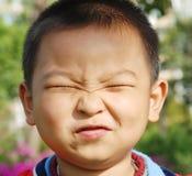 Um menino impertinente que faz a face foto de stock royalty free