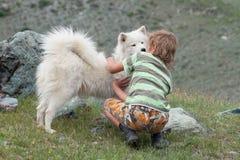 Um menino joga com um cão de puxar trenós do cão Imagem de Stock Royalty Free