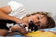 Um menino joga com um gato fotografia de stock