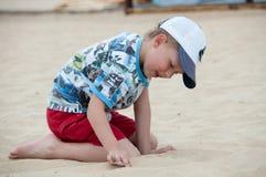 Um menino joga na areia na praia Imagens de Stock Royalty Free