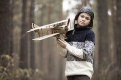 Um menino joga nas madeiras com um plano do brinquedo jogos do outono no w fotos de stock